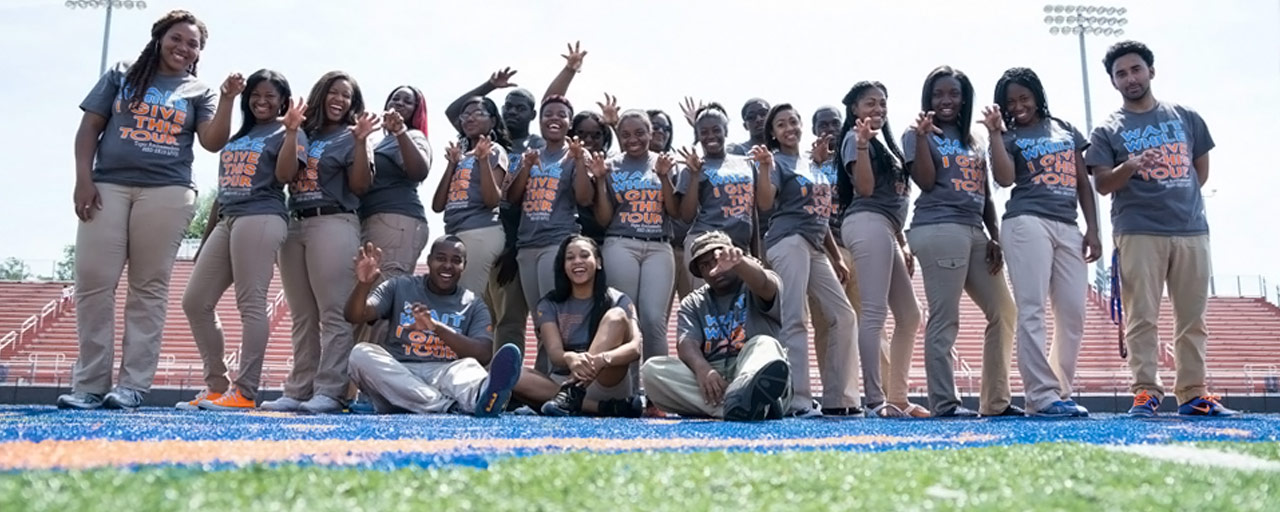 Savannah State University's Tiger Ambassador students posing with claws on the football field.
